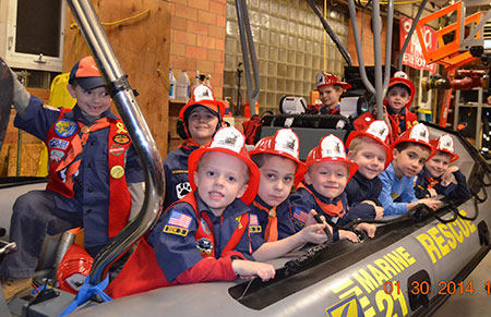 Cub Scouts sit in a rescue raft in the Thompsonville Fire Station