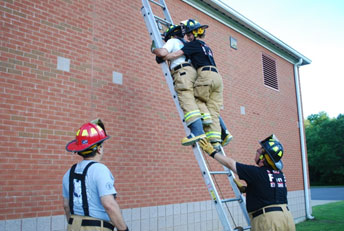 A firefighter trains to rescue people on a ladder