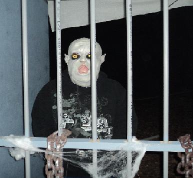 A ghoulish prisoner sits behind bars