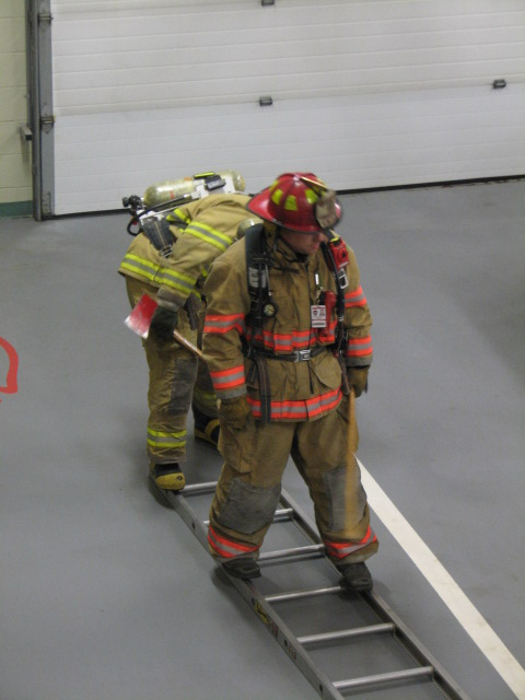 Two firefighters walk on a ladder placed on the floor