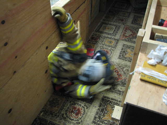 A firefighter pushes through a low hole in the wall to get through The Maze