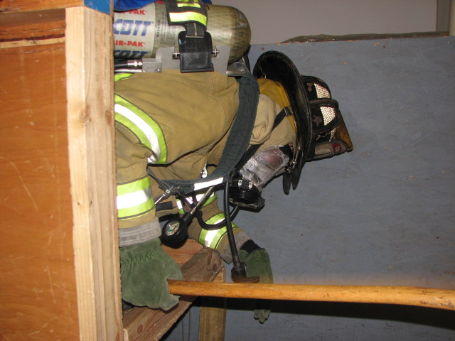 A firefighter starts to crawl through The Maze