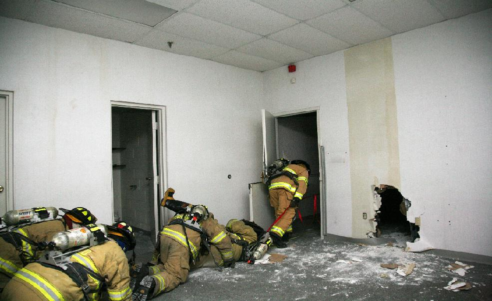 The firefighters work to get the fire victim out of danger