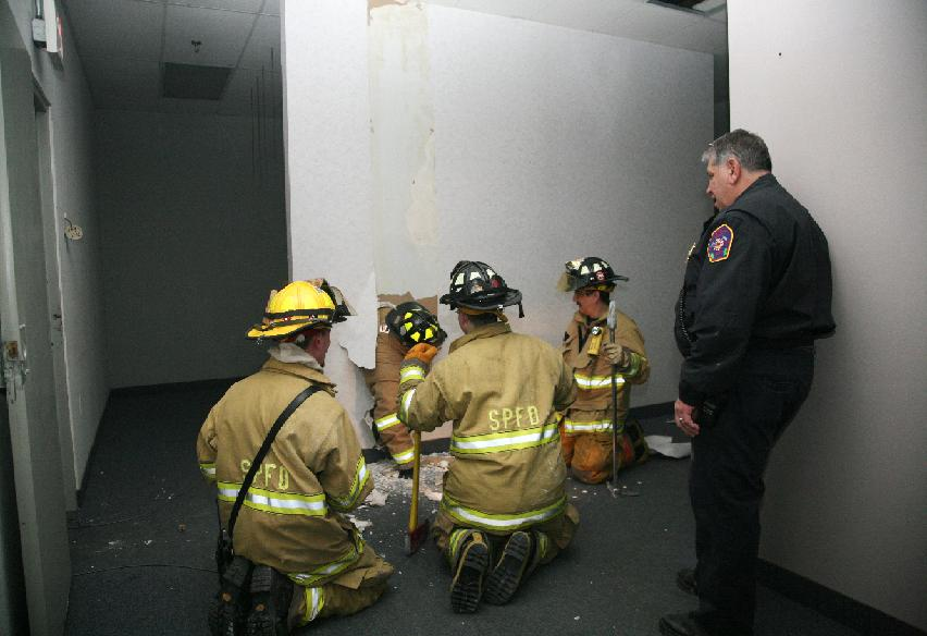 A group of firefighters wait on the other side of the wall for the rest of their group