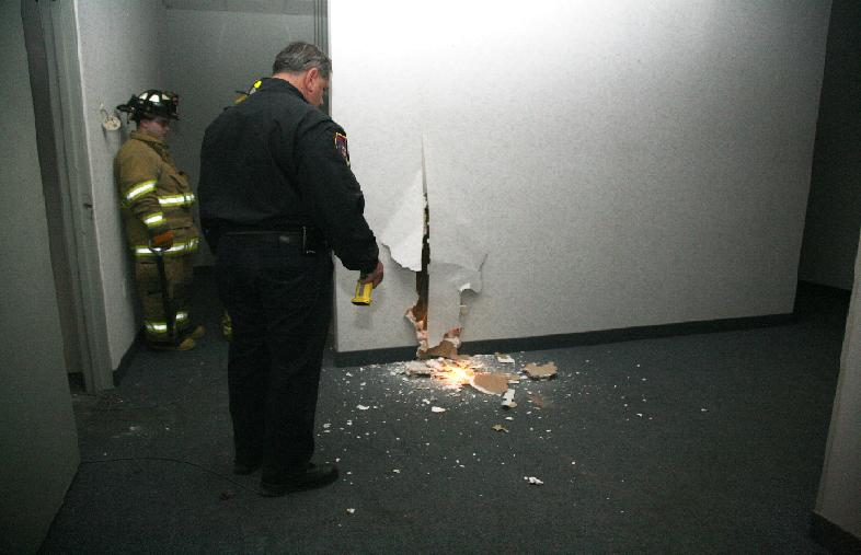 Firefighters cut a hole through the wall