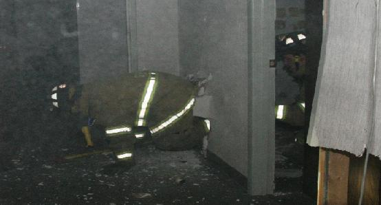 A firefighter crawls through the wall