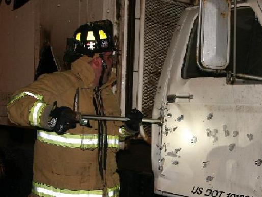 A firefighter uses a different tool to pry open the door