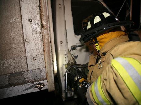 With the tool forced into the door firefighters work to get it open