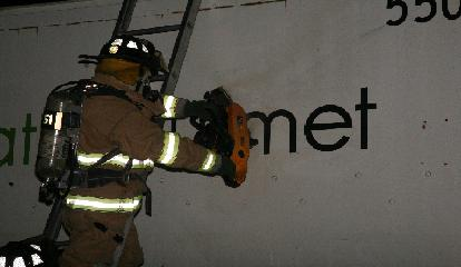 A firefighter prepares to cut a hole in the side of a truck