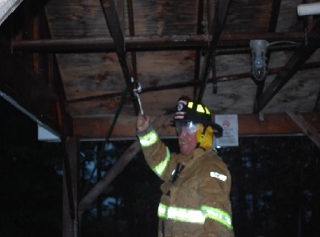 Firefighter Blinn smiles after getting the sprinkler under control