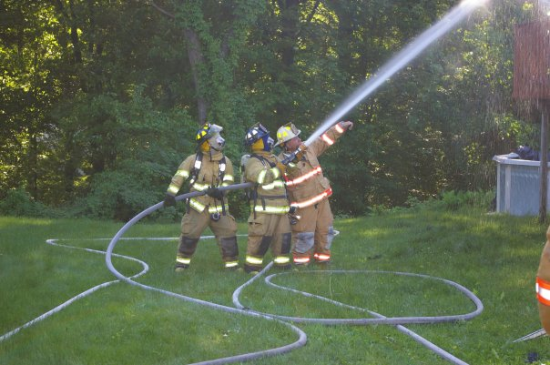 Firefighters work together to spray water onto the fire