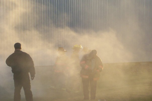 Firefighters walk through the smoke from the magnesium fire