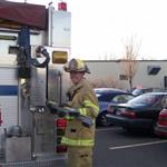 A firefighter smiles for the camera as he gets equipment from the fire engine