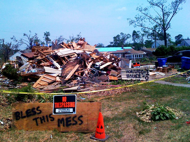 "Signs stand around a pile of rubble, one of which reads ""Bless This Mess,"" another ""Tornado 1, House 0"""