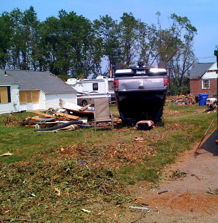 A truck lays upside down in a yard after a tornado