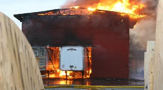 Semi-truck trailers sit in the garage as it burns around them