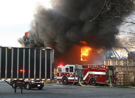 A Hazardville fire engine sits in front of the burning building