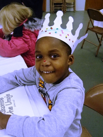 A young girl participates in an activity while wearing a crown