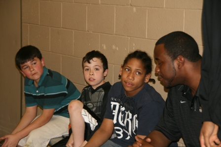 A CCSU player speaks with some children at the event
