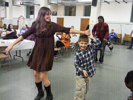 A young boy dances with a young lady