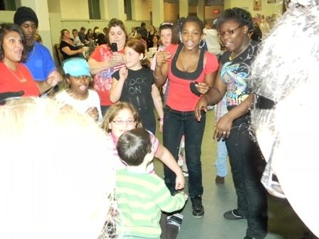 The children at the event come together to dance and talk