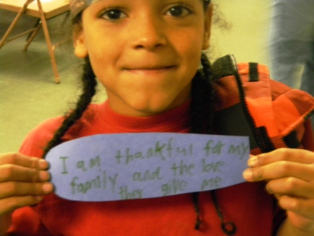 "A young child holding a paper feather which says ""I am thankful for my family and the love they give me"""