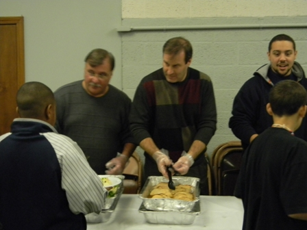 Volunteers serve dinner to participants