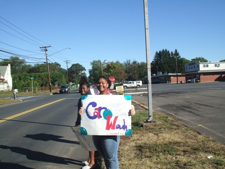 Girls hold signs for the car wash