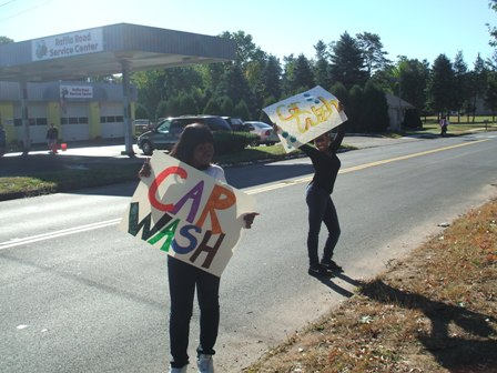 "Two young ladies try to get the attention of passing cars while holding ""Car Wash"" signs"