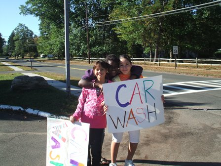 "Two young ladies hold ""Car Wash"" signs for the event"