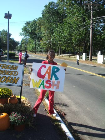 "A young lady holds a colorful ""Car Wash"" sign"