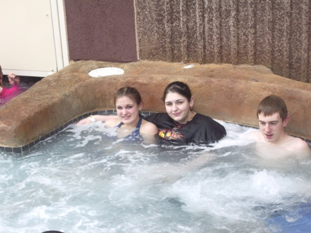 Kids sit together in the hot tub enjoying the bubbles