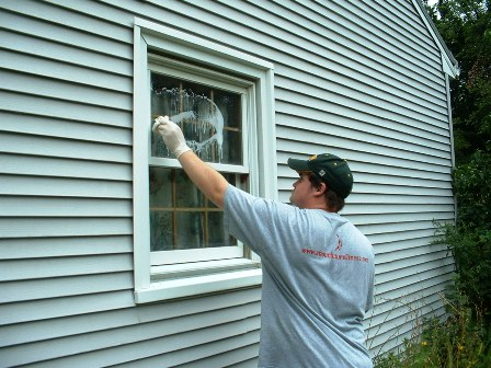 A club member washes the windows of a house