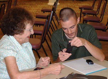 A club member teaches a senior citizen how to use her cell phone