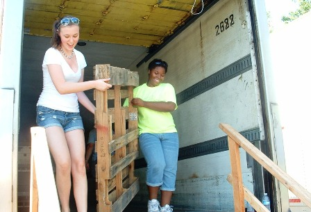 Club members help unload pallets from the back of a truck