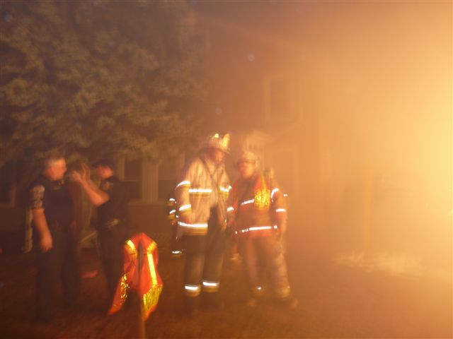 Emergency personnel talk together to find the best way to put out the fire