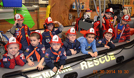 Cub Scouts sit in a rescue raft at the Thompsonville Fire Station